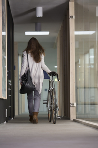 Business woman leaving office with racing cycleの写真素材 [FYI04339037]