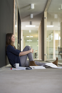 Portrait of business woman sitting on ground in corridor ofの写真素材 [FYI04339039]