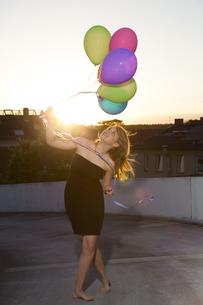 Teenage girl standing with balloons outdoorsの写真素材 [FYI04339053]
