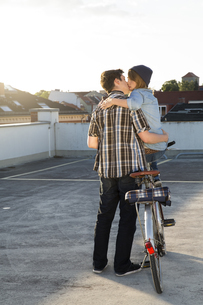 Teenage couple with bicycle kissing outdoorsの写真素材 [FYI04339054]