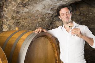 Man in wine cellar tasting wineの写真素材 [FYI04339100]