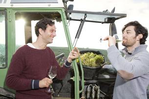 Germany, Bavaria, Volkach, two winegrowers tasting white winの写真素材 [FYI04339104]