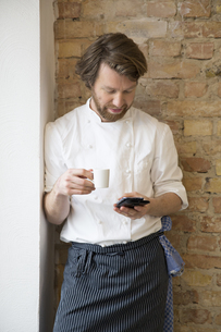 Cook with espresso cup and smartphone having a restの写真素材 [FYI04339137]