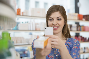 Portrait of woman comparing products in a pharmacyの写真素材 [FYI04339149]