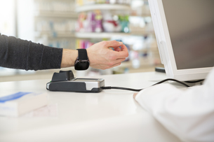 Customer paying cashless with smartwatch in a pharmacyの写真素材 [FYI04339150]