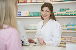 Portrait of smiling female pharmacist advising female customの写真素材 [FYI04339153]
