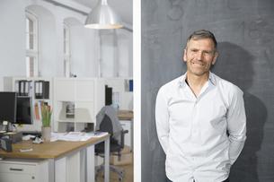 Smiling mature man standing at blackboard in officeの写真素材 [FYI04339182]
