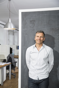 Smiling mature man standing at blackboard in officeの写真素材 [FYI04339183]