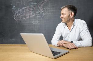 Smiling mature mman with laptop at blackboardの写真素材 [FYI04339186]