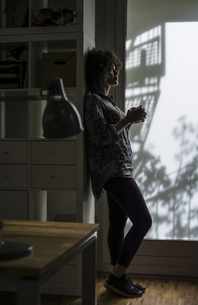 Young woman with cup of coffee leaning against cabinetの写真素材 [FYI04339190]
