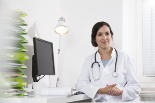 Portrait of smiling doctor sitting at deskの写真素材 [FYI04339205]