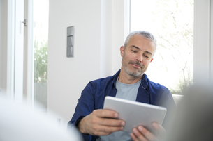 Mature man working from home using digital tabletの写真素材 [FYI04339222]