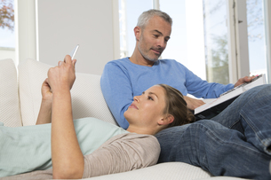 Couple relaxing on couch at home reading book and ebookの写真素材 [FYI04339228]