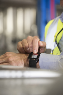 Man using smartwatch in industrial plantの写真素材 [FYI04339252]