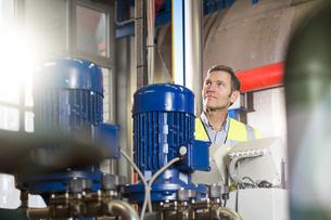 Man wearing reflective vest looking around in industrial plaの写真素材 [FYI04339253]