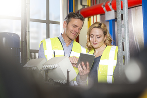 Colleagues wearing reflective vests sharing digital tablet iの写真素材 [FYI04339255]