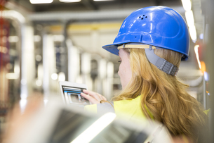 Woman wearing reflective vest controlling industrial plant wの写真素材 [FYI04339256]
