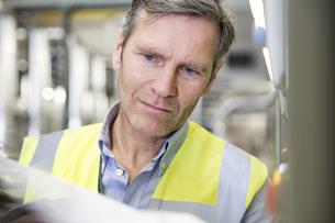 Man wearing reflective vest in industrial plantの写真素材 [FYI04339260]