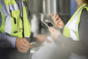 Colleagues wearing reflective vests talking in industrial plの写真素材 [FYI04339266]