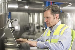 Man wearing reflective vest using laptop in industrial plantの写真素材 [FYI04339267]