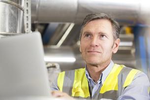 Man wearing reflective vest using laptop in industrial plantの写真素材 [FYI04339268]
