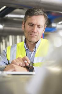 Man using smartwatch in industrial plantの写真素材 [FYI04339270]