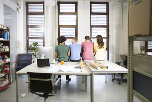 Team of creative professionals sitting on desk in officeの写真素材 [FYI04339281]
