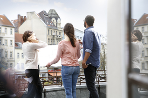 Man and two women standing on roof terrace looking at planの写真素材 [FYI04339296]