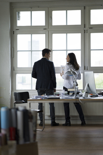 Businessman and woman standing at office window, disussingの写真素材 [FYI04339299]