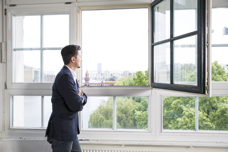 Businessman standing at open window with arms crossedの写真素材 [FYI04339307]
