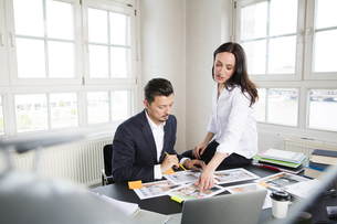 Businessman and woman sitting at desk in office, working togの写真素材 [FYI04339309]