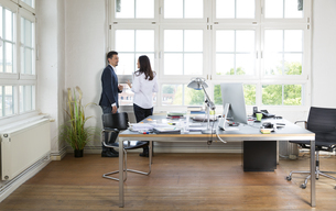 Businessman and woman standing at office window, disussingの写真素材 [FYI04339311]