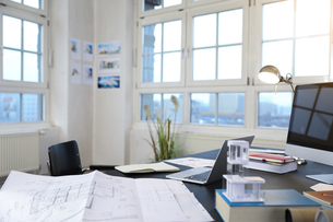 Desk with construction plan in a modern informal officeの写真素材 [FYI04339338]