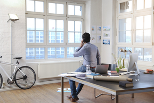 Man using cell phone in a modern informal officeの写真素材 [FYI04339342]