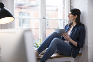 Woman with tablet looking out of window in officeの写真素材 [FYI04339347]