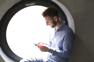 Smiling man sitting in round window looking at cell phoneの写真素材 [FYI04339350]