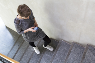 Woman walking upstairs using cell phoneの写真素材 [FYI04339354]