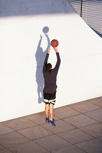 Young man playing basketball in the cityの写真素材 [FYI04339355]