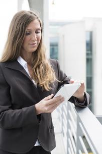 Germany, Berlin, Businesswoman using digital tablet, smilingの写真素材 [FYI04339360]