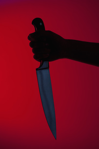 Human hand holding kitchen knife against red backgroundの写真素材 [FYI04339365]