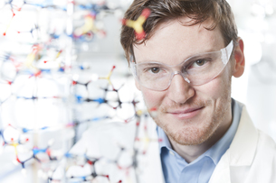 Germany, Portrait of young scientist with DNA model, smilingの写真素材 [FYI04339372]