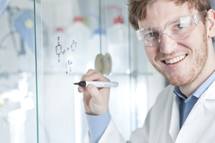Germany, Portrait of young scientist writing chemical equatiの写真素材 [FYI04339376]