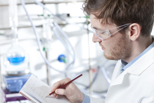 Germany, Portrait of young scientist making notes in bookletの写真素材 [FYI04339377]