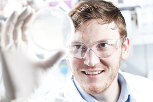 Germany, Young scientist checking petri desh, smilingの写真素材 [FYI04339379]