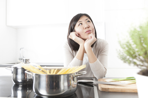 Portrait of pensive young woman cooking spaghettiの写真素材 [FYI04339400]