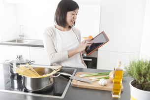Smiling young woman using digital tablet while cookingの写真素材 [FYI04339404]