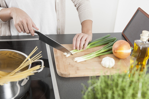 Young woman cutting spring onions on wooden boardの写真素材 [FYI04339406]
