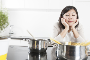 Portrait of smiling young woman relaxing while cookingの写真素材 [FYI04339408]