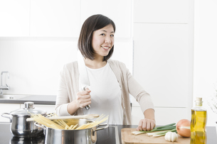 Portrait of smiling young woman cookingの写真素材 [FYI04339409]