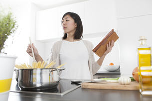 Young woman holding digital tablet while cooking spaghettiの写真素材 [FYI04339412]